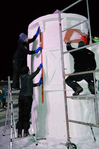 Sculptors work to finish the Budweiser sculpture Friday night.