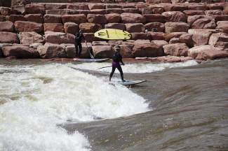 Host Shawna Henderson (on water) gets tips from Glenwood Springs-area SUP instructor Charlie MacArthur on the wave at the Glenwood kayak park. The park, found on the Colorado River minutes from downtown, is one of the best places in the state for surfing on a SUP board.