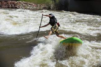 A SUP paddlers gets caught in a wave at the Glenwood Springs kayak park, found minutes from downtown. SUP gives veteran whitewater gurus a chance to have fun again on Class I and Class II waters, or just test their mettle on the intimidating surf waves at the park.
