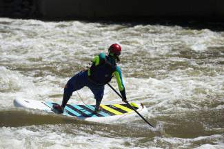 A SUP rider surfs the waves at the Glenwood Springs kayak park. The park is home to some of the best surfing in Colorado for adventurous whitewater SUPers in need of a little ocean-style action.
