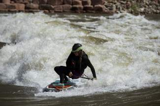 A SUP paddler gets low on the wave at Glenwood Springs. The wave is one of the best kayak parks in Colorado, built directly into the Colorado River just minutes from downtown Glenwood.