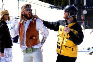 Kelly Lundeen, left, 25, of Loveland, is jokingly harassed by Dan Williams, 28, of Breckenridge, at Arapahoe Basin Ski Area on Wednesday, April 1, 2015. Lundeen wore a dreamcatcher from one ear while Williams sports a borrowed ski resort mountain safety jacket.