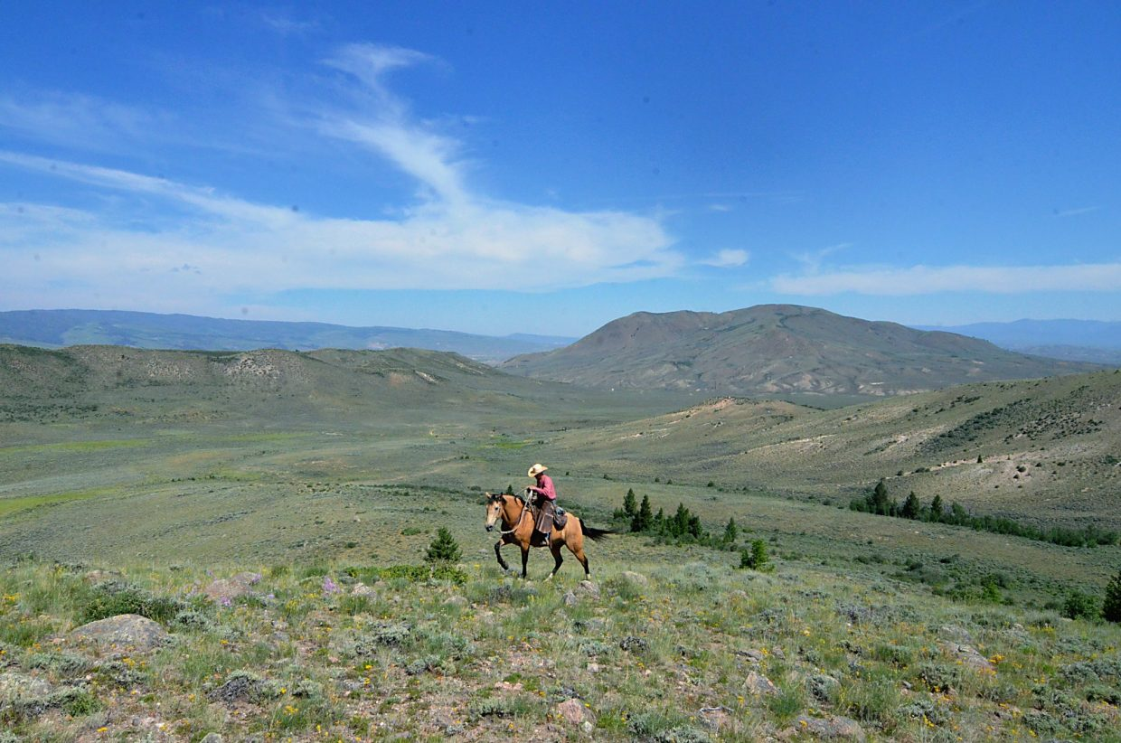 Rusty Spurr Ranch owner Han Smith sits atop Hooligan during a cattle drive. The ranch is just south of Kremmling, at the base of the Williams Fork mountain range.