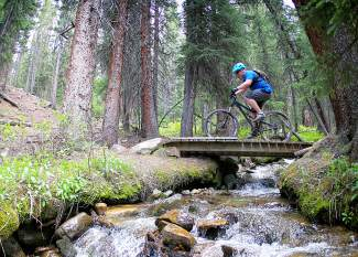 A rider on the trails at Copper Mountain. Each of Copper's trails weave across the mountain through a mix of pine forests and mountain meadows. The mountain plays host to the brand-new Copper Crush mountain bike races on July 30.