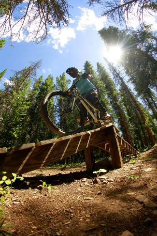 A mountain biker on an A-frame log feature at Copper Mountain. The resort is home to the brand-new Copper Crush mountain bike races on July 30.