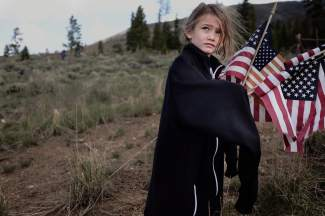Five-year-old Danika Barth of Silverthorne helps plant American flags on the graves of U.S. military veterans at the Memorial Day ceremony at Dillon Cemetery on Monday, May 30.