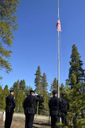 Members of the color guards for the Breckenridge Police Department and Red, White and Blue Fire raise a flag to half-staff during a Memorial Day commemoration event at Valley Brook Cemetery on Monday, May 30.