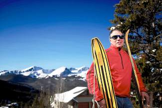Greg Gutzki outside of his home at the base of Baldy Mountain with two relics of winter sports history: an original Snurfer (left), his Christmas gift in 1966, and a pair of Miller Soft powder skis (right) from the 1980s.