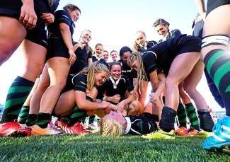 The Summit High School rugby shares a laugh as their teammate Elle Scott-Williams cramps up while celebrating their 64-7 win over Chaparral at Infinity Park in Denver to claim their eighth straight state championship in November. This May, the Tigers took second at the High School National Championships, the final high school game for three seniors heading to Division I rugby programs next season.