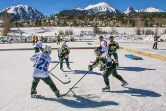 Players in the Pabst division reach for the puck under bluebird skies at the Pabst Blue Ribbon Colorado Pond Hockey Tournament on Feb. 13. The seventh annual tournament, held at North Pond Park in Silverthorne, drew 150 teams and more than 900 players from 45 states for three days of round-robin play and plenty of PBR.