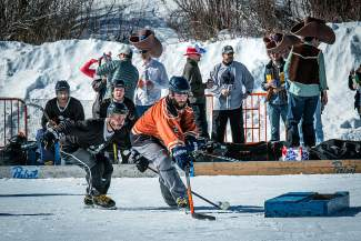 A player reaches for a goal with costumed cowboys (aka the Ten Gallon Hat Trick crew from Austin) in the background at the Pabst Blue Ribbon Colorado Pond Hockey Tournament on Feb. 13. The seventh annual tournament, held at North Pond Park in Silverthorne, drew 150 teams and more than 900 players from 45 states for three days of round-robin play and plenty of PBR.