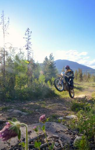 Tim Nixon, president of Summit County Off-Road Riders, pops a wheelie on a moto trail in the Frisco area.