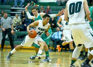Summit's Jesus Moya (10) dribbles past a Delta defender at a home boy's basketball game on Jan. 15. The Tigers lost, 61-46.
