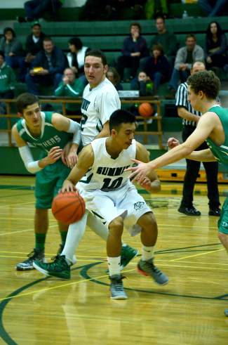 Summit's Jesus Moya (10) looks for a lane past a Delta defender during a boy's basketball game at home on Jan. 15. The Tigers lost, 61-46.