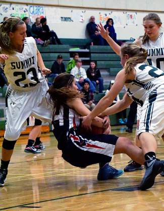 Eagle Valley's Victoria Schwaiger, center, takes the ball to the hardwood with a trio of Summit players swarming to defend during a Tigers home game on Jan. 8, shot by @louietraub
