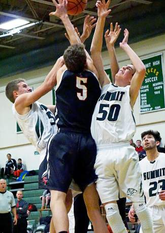 Summit's Turner McDonald, left, and Andrew Shaw, right, go after a loose ball with Eagle Valley's Dawson Keller during the second half of the Tigers' 48-42 win at home on Jan. 8. It was the first win of the season for the boy's basketball team.