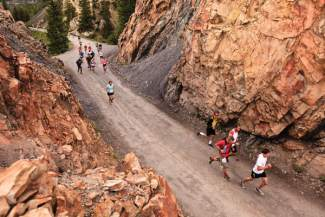 A group of foot racers winds through one of several rock formations on Boreas Pass Road. The road was once a railroad for miners and mining equipment in the late 1800s.
