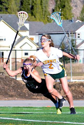 Summit's Maddy Remias and a Grand Junction attacker collide during the first half of a girl's varsity lacrosse game at home on May 3. The Tigers lost, 7-10.
