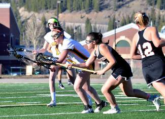 Summit's Lillian Walker and a Grand Junction attacker vie for the ball at a girl's varsity lacrosse game in Frisco on May 3. The Tigers lost, 7-10.