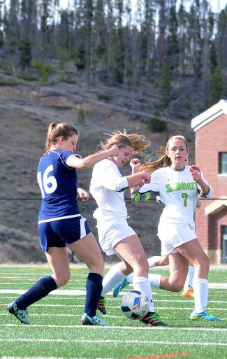 Summit senior Katie Sullivan (9) and freshman Sydney Kerstiens (7) battle for the ball with a Rifle defender at home shortly before Sullivan scored the game-winning goal in OT, captured by @sumcosports