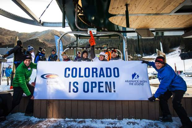 Arapahoe Basin COO Alan Henceroth (far right) holds the opening day banner for the first chair of the 2016-17 ski season before Black Mountain Express started spinning at 9 a.m. on Oct. 21. Roughly 3,000 skiers and snowboarders descended on A-Basin for a single run, High Noon, under cloudless skies.