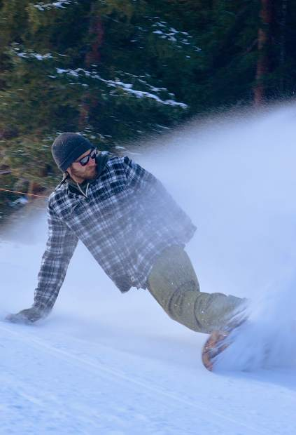 A snowboarder sprays a cameraman offscreen early in the morning of opening day at Arapahoe Basin on Oct. 21. The ski area saw rouhgly 3,000 skiers and snowboarders during the day for riding on a single run under clear, blue skies.