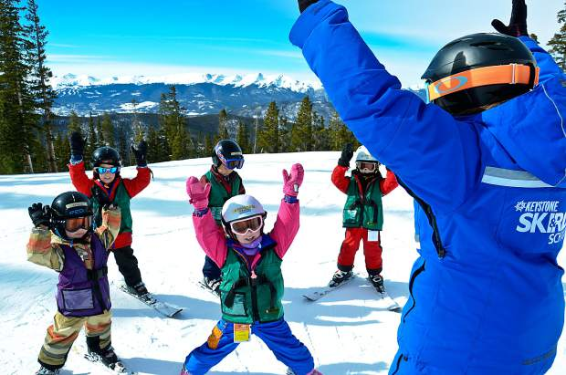 A ski instructor guides young students through a few flat-land exercises before heading onto the snow. Local thrift and consignment stores are great places to begin looking for affordable kid's ski clothing before the season begins.