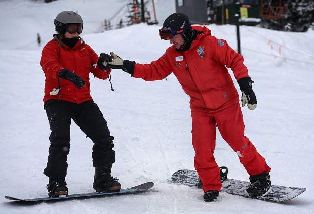 A snowboard instructor helps a client learn to slip down the slopes during a lesson at Copper Mountain. Local pros and instructors suggest taking a lesson for your first day on a board to learn proper technique.