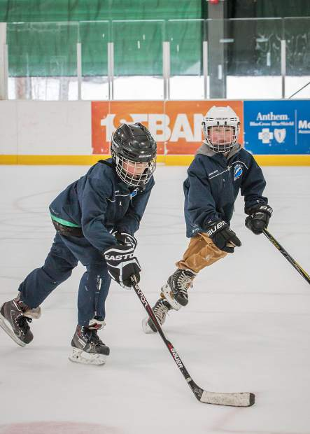 Local youngsters and Summit Youth Hockey Squirt players Blake Postles (left) and Graham Schuman (right) take time during the Summit School District break to practice their skills at the newly covered outdoor rink at the Stephen C. West Ice Arena. complex.