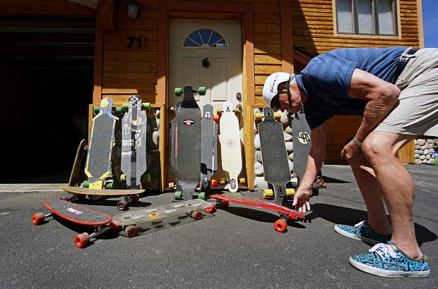 Summit local Jim Bowden with his collection of longboards and vintage skateboards. The boards range from '60s-era penny boards with clay wheels and steel trucks to brand-new Never Summer decks, including a few Bowden cut and assembled from scratch in his garage.