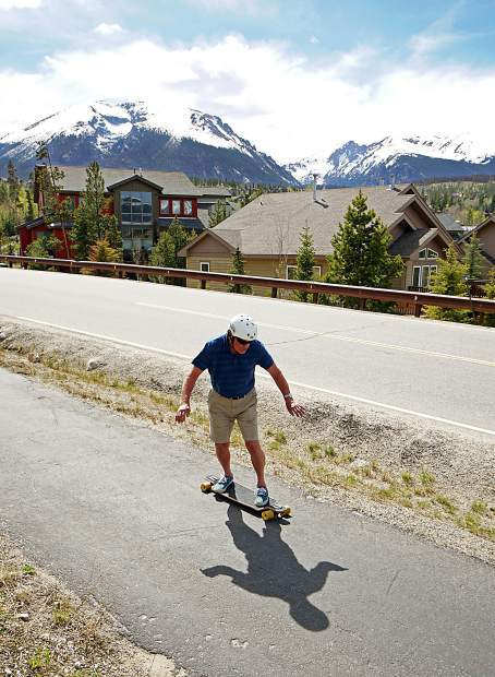 Summit local Jim Bowden cruises down the sidewalk near his home in Wildernest with Buffalo Mountain and Red Peak in the background. The 74-year-old lifelong skateboarder still gets one or two days per week on his longboard when summer arrives.