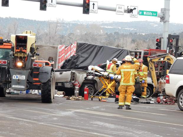 Emergency responders enlisted a large fork lift to try to stabilize the sheetrock that fell on a pickup, pinning the driver.