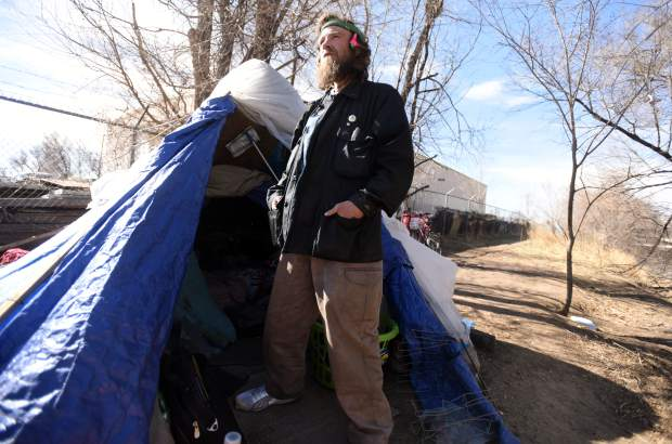 Wesley Waldvogle stands outside his tent off Poudre River this past month in Greeley. Waldvogle doesn't identify as a veteran, though he served in the Army. He says he doesn't want a house, a normal job or a lot of money. He only wants to live on the land and make just enough to get by.