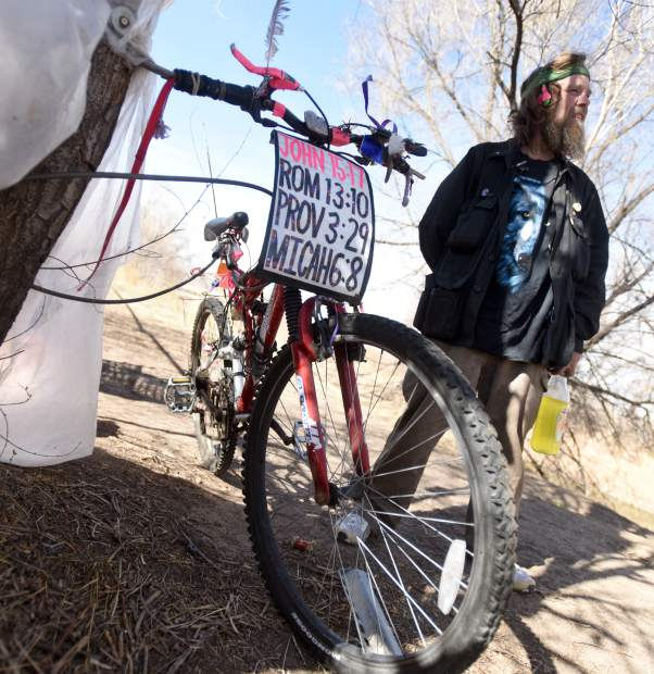 A sign shows off a few Bible verses Wesley Waldvogle memorized as he stands by his camp along the Poudre River this past month in Greeley. Wesley was removed from his camp the following day.
