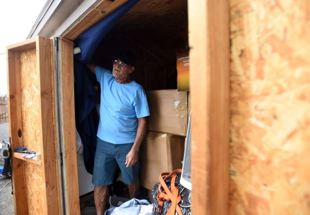 John Delgado pulls back a sheet that blocks the light from entering his shed in Evans.