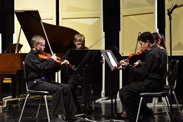 "With Malachi Ryan, center left, Isabella Huhn, back right, and Isaac Webster, right, Caleb Arthurholt performs his original composition, ""Quartet for Violins,"" during the third annual Young Composers Competition Concert on Monday at Summit Middle School in Frisco."