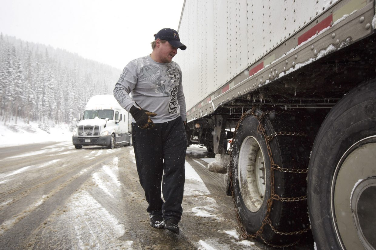 A truck driver install chains to his semitrailer Thursday, May 18, 2017, along Interstate 70 on Loveland Pass.