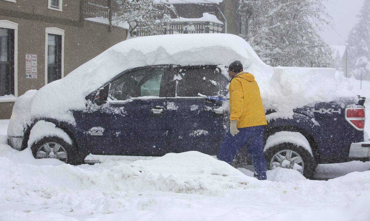 A visitor brush snow off his vehicle along Main Street Thursday, May 18, 2017, in Frisco.