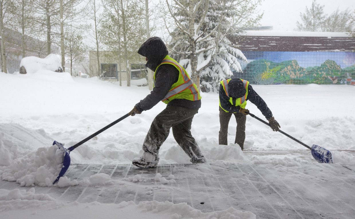 Town of Frisco employees Calle McCartney, left, and Chris Irwin shovel snow along Main Street Thursday, May 18, 2017, in Frisco.