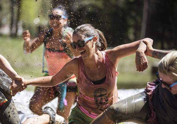 Mud runners laugh and smile as they barrel through mud pits during the 2017 Dirty Girl Mud Run at Copper Mountain on June 10. The event drew hundreds of female runners from across the state and globe for a 5K benefit to support Boarding for Breast Cancer, a California nonprofit that pairs breast cancer survivors with snowboarding, skateboarding, surfing and mud running.