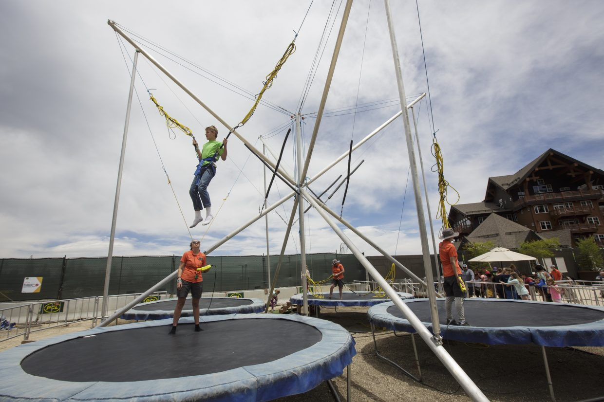 Guests use the bungee trampoline during the opening day of Epic Discovery summer theme park Friday June 9, on Breckenridge Ski Resort.