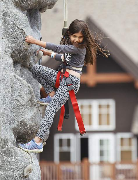 Liviana Olivetti, 7, of Denver, looks down from atop of the
