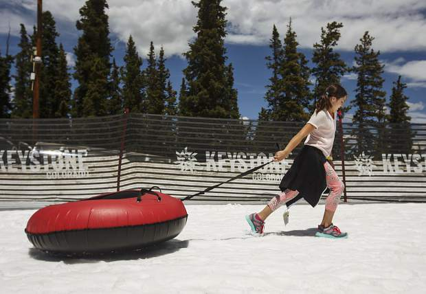 A young visitor drags her snowtube towards the top of the hill for a thrill ride down Tuesday, June 20, at Keystone Ski Resort.