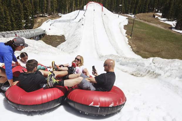 A group of four thrill-seekers prepare to drop from top of the snow tubing hill Tuesday, June 20, at Keystone Ski Resort.