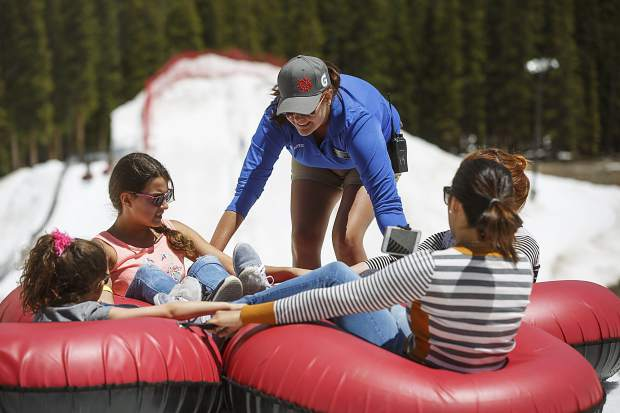 Keystone Snow Tubing attendant, middle, prepares a group of four guests for a slide from top of the snow tubing hill Tuesday, June 20, at Keystone Ski Resort.