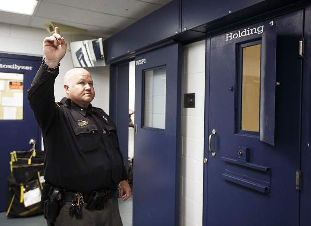 Summit County jail commander Erik Bourgerie signals toward a security camera to open a holding cell Wednesday May 31, 2017, at the jail in Breckenridge.