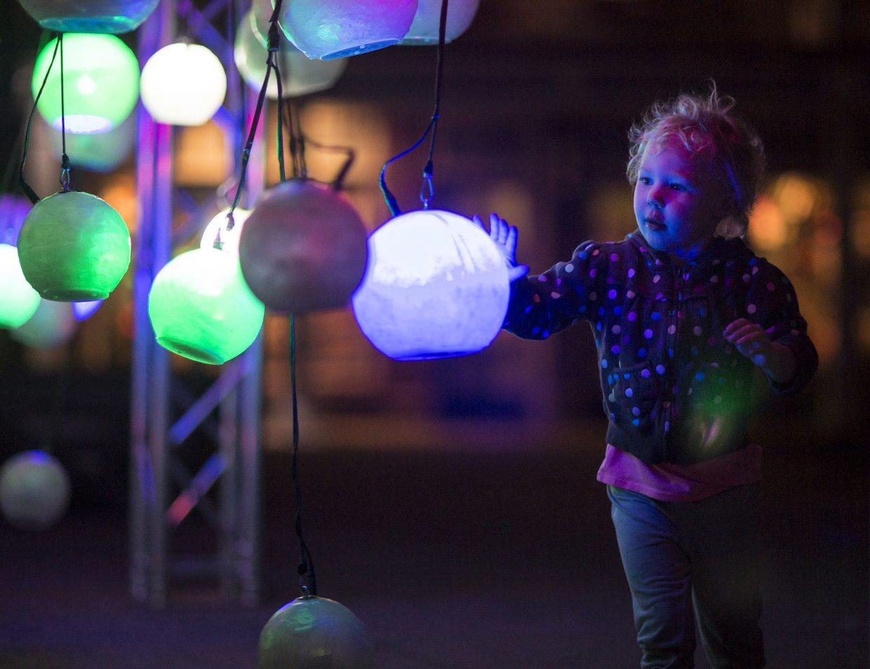 Oaklee Emore, 3, interacts with a suspended globe during the BreckCreate's WAVE festival at the Blue River Plaza Thursday June 1, 2017, in downtown Breckenridge.