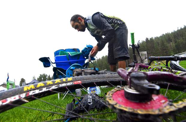 A rider washes off at Carter Park as his hard-tail gets a break between loops one and two at the Breck 100 on July 29. The event drew nearly 300 riders from across the world for 32, 68 and 100 mioles of riding in constant rain and chilly temperatures.