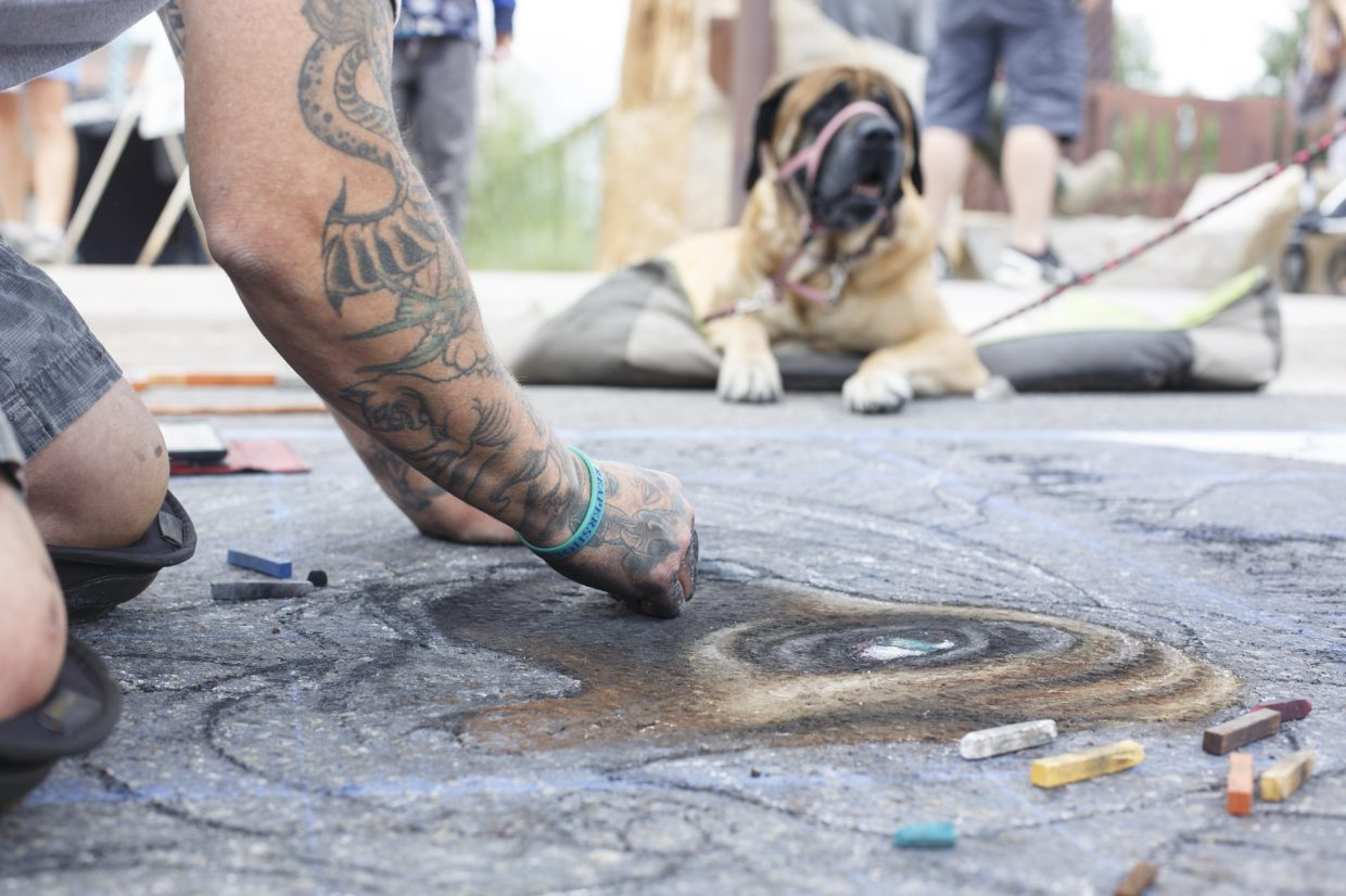 Artist Jim Karanik draws Josie, an English mastiff, with chalk during the Street Art Festival Monday, July 2, in Breckenridge Arts District. The free celebration of street and graffiti arts featuring outdoor murals, chalk installations, and performances is on display in the Breckenridge Arts District July 4 from noon to 4 p.m.