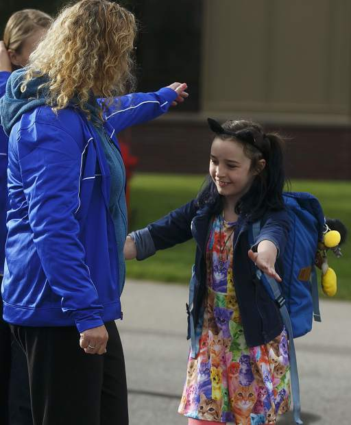 Silverthorne Elementary fifth grade student Kyah Quam, right, reaches out to hug staff member Susan Maar upon arriving for the first day of in front of the school on Thursday morning, Aug. 24.